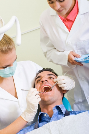 dentist and assistant working on male patient photo
