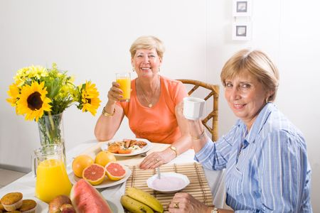 happy senior sisters having breakfast photo