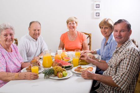 group of senior friends having breakfast together photo