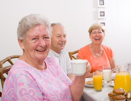 male senior adult: happy seniors friends having breakfast together