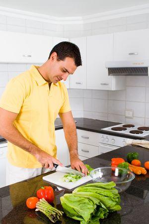 unmarried: joven haciendo ensalada saludable en la cocina moderna