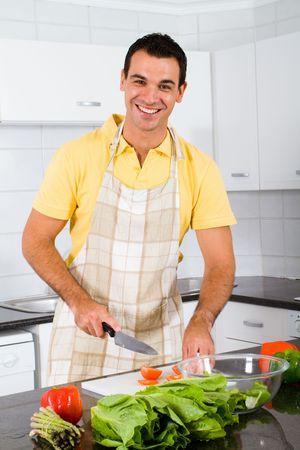 unmarried: joven feliz, preparar la comida en la cocina