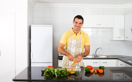 happy young man preparing food in kitchen photo