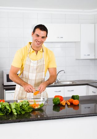 холостяк: happy bachelor cooking in kitchen