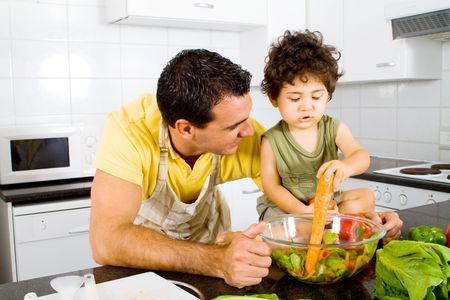 father and son cooking in modern kitchen photo