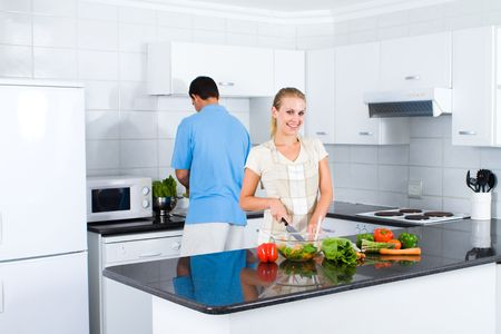 happy young woman and boyfriend cooking food in kitchen photo