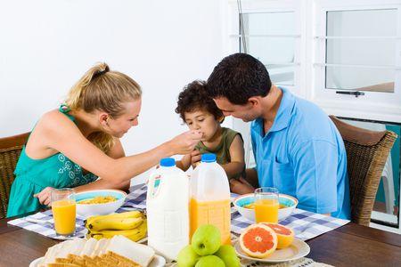 mother feeding breakfast to baby boy photo