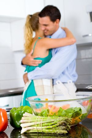 vegetables young couple: happy lovely young couple hugging in kitchen, focus is on the asparagus Stock Photo