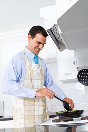 middle eastern food: young man stir fry vegetable in kitchen Stock Photo