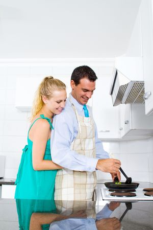 young couple cooking dinner at home photo