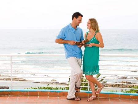 young couple drinking coffee on balcony with sea view behind Stock Photo - 6500165