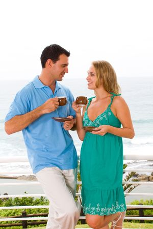 young couple drinking coffee on balcony with sea view behind photo