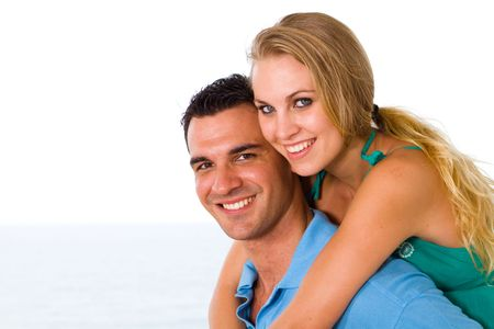 happy young couple piggyback with beautiful sea view behind photo