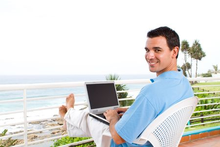 casual businessman using laptop on balcony with sea view behind photo