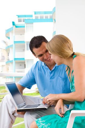 young couple using laptop on balcony photo