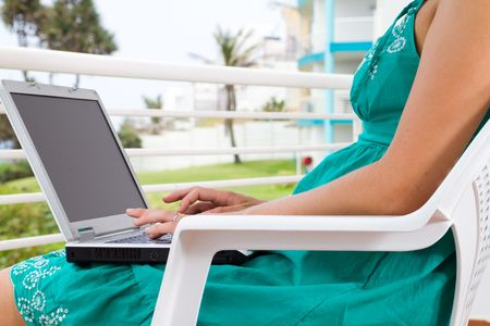 young woman using laptop on home balcony photo