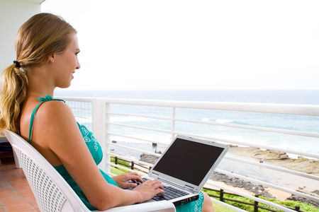 balcony view: young woman using laptop on home balcony