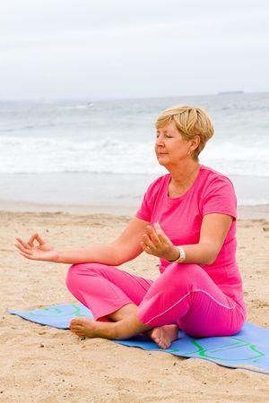 senior woman on beach meditation photo