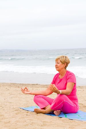 senior woman on beach meditation photo