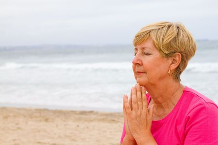 thoughtful senior woman on beach meditation photo