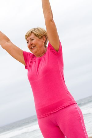 senior woman doing fitness exercise on beach photo