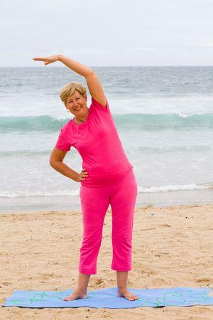senior woman exercise on beach photo