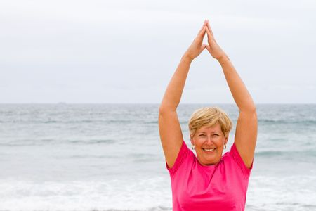 happy and healthy senior woman exercise on beach photo
