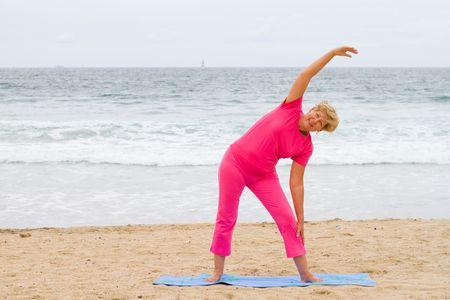 senior woman doing exercise on beach photo