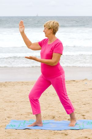 tai chi: senior woman doing Tai Chi exercise on beach