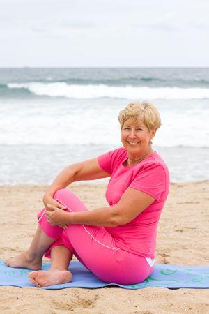 senior woman stretch on beach while sitting on mat photo