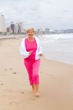 senior exercise woman jogging on beach photo