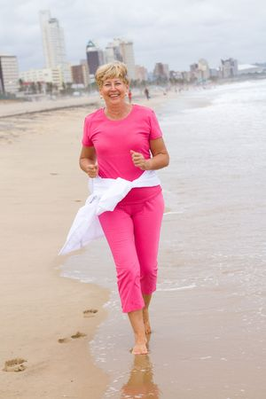 happy senior exercise woman running on beach photo
