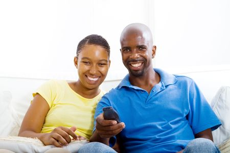happy african couple watching tv photo
