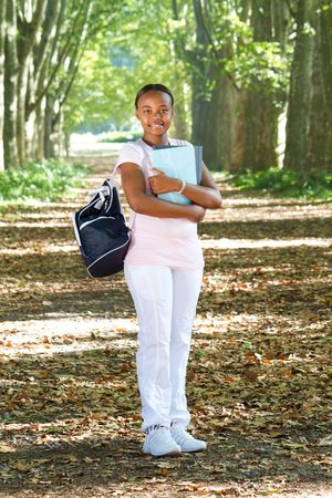 happy young student in park with notebooks photo