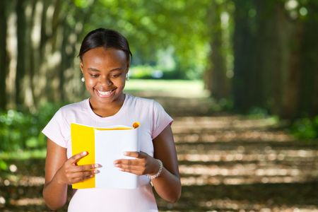 smiling african american student reading in park Stock Photo - 6652118