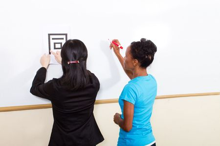 chinese american: teacher helping student learn chinese writing