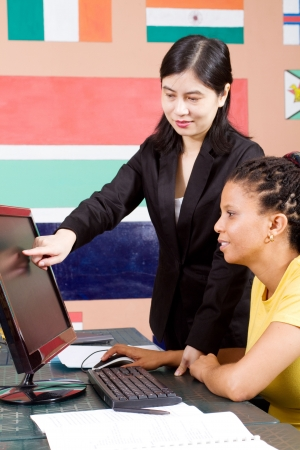 advising: chinese teacher helping african adult student on computer Stock Photo