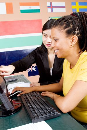 teaching adult: female chinese teacher teaching adult african student Stock Photo
