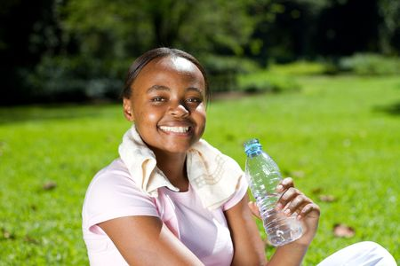african woman drinking water in the park photo