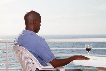 african man relaxing with glass of wine Stock Photo