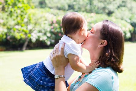 mother kissing baby daughter photo