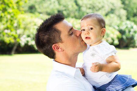 toddler walking: father kissing daughter Stock Photo