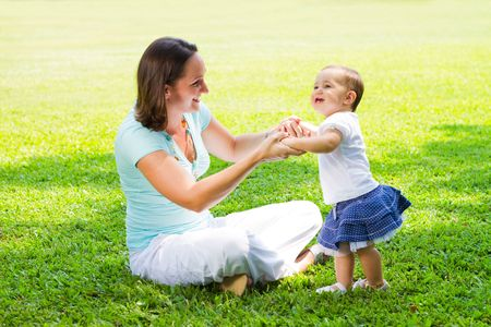 toddler walking: mother and daughter playing in park
