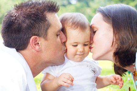 cheek to cheek: parents kissing baby daughter