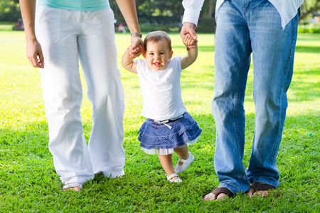 parents walking with child in park photo