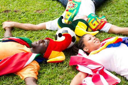fandom: group of soccer fans lying on grass Stock Photo