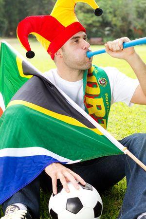 fanatical: south african soccer fan blowing vuvuzela Stock Photo