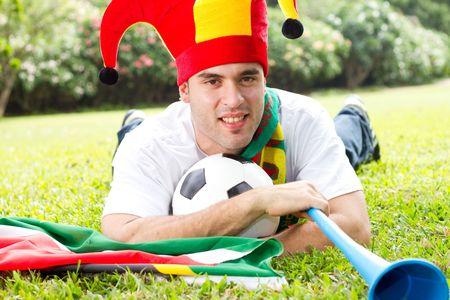 fanatical: soccer fan lying on green grass