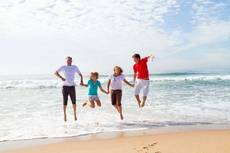 family jumping in waves on beach photo