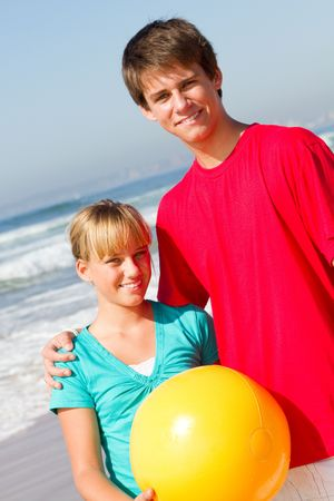 spunky: brother and sister on beach with ball Stock Photo